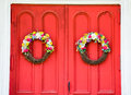 Weathered bright red church door with flower wreaths Royalty Free Stock Photo