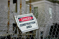 Weathered danger construction area sign a weather damaged mounted at an angle on a chain link fence Royalty Free Stock Image