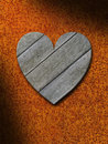 Weathered gray wood heart against rusty metal background Stock Photo