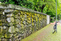 Weathered Stone Wall and Brick Sidewalk Stock Photo