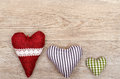Weathered wooden board with three hearts of cloth Royalty Free Stock Photos