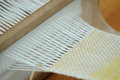 Weaving traditional loom with white yellow yarn Stock Image