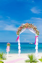 Wedding arch cabana gazebo on tropical beach decorated with flowers decoration Stock Photos