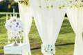 Wedding arch with flowers and сandle decoration on sunny day in ceremony place Royalty Free Stock Photo