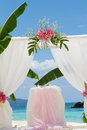 Wedding arch tent decorated with flowers on beach tropical ceremony set up Royalty Free Stock Image