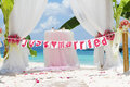 Wedding arch tent decorated with flowers on beach tropical ceremony set up Royalty Free Stock Images
