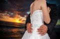 Wedding on the beach groom holding bride at sunset Stock Photo