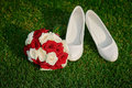 Wedding bouquet and the bride& x27;s white shoes on grass Royalty Free Stock Photo