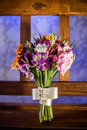 Wedding bouquet a colorful on a wooden bench with purple lit background Royalty Free Stock Image