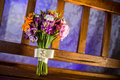 Wedding bouquet a colorful on a wooden bench with purple lit background Royalty Free Stock Photography