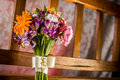 Wedding bouquet detail a colorful on a wooden bench with lit background Royalty Free Stock Photography