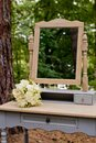 A wedding bouquet in the forest on a table with a mirror. Wedding decorations Royalty Free Stock Photo