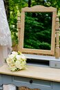 A wedding bouquet in the forest on a table with a mirror. Royalty Free Stock Photo
