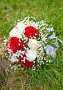 Wedding bouquet in the grass on a green meadow red and white roses Stock Photos