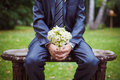 Wedding bouquet groom sitting on a banch in a summer park and holding selective focus on Royalty Free Stock Photography
