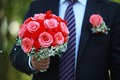 Wedding bouquet in his hand red round a of the groom a dark suit Stock Photo