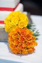 Wedding bouquet of orange and yellow roses by a cake Stock Photo