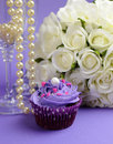 Wedding bouquet with purple cupcake closeup of white roses and pearls in champagne glass against lilac background vertical close Stock Image