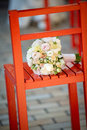 Wedding bouquet on a red chair lying location Royalty Free Stock Image