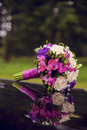 Wedding bouquet with red roses laying on car Royalty Free Stock Image