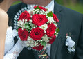 Wedding bouquet with roses against the background of the groom red in hand bride Stock Photo