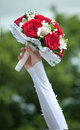 Wedding bouquet with roses red in hand of the bride Stock Photo