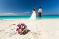 Wedding bouquet on wedding couple background kissing at the beach Stock Images