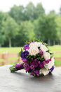 Wedding bouquet of white and blue roses lying on wooden surface Royalty Free Stock Photography