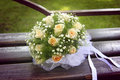 Wedding bouquet with white bow lying on a bench Royalty Free Stock Photos