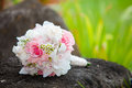 Wedding bouquet with white and pink roses is lying on the rock Royalty Free Stock Image