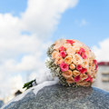 Wedding bouquet of yellow and pink roses lying on granite Stock Photo