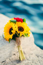 Wedding bridal bouquet of sunflowers on the dock near the sea. W Royalty Free Stock Photo