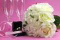 Wedding bridal bouquet of white roses on pink background with pair of champagne flute glasses and gold wegging ring in black Royalty Free Stock Photo