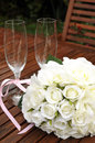 Wedding bridal bouquet of white roses with two champagne glasses pink polka dot ribbon on outdoor garden table setting after Stock Image