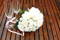 Wedding bridal bouquet of white roses with two champagne glasses with pink polka dot ribbon on outdoor garden table setting after Stock Image