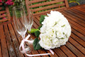 Wedding bridal bouquet of white roses with two champagne glasses with pink polka dot ribbon on outdoor garden table setting after Stock Images