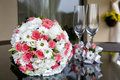 Wedding bridal bouquet and wine glasses on a table near the newlyweds home Royalty Free Stock Photography