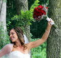 Wedding bride portrait with flowers in hand and a forest background Royalty Free Stock Photography