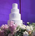 Wedding Cake with beautiful flowers decoration at the stage in front of purple light backdrop in wedding reception night ceremony Royalty Free Stock Photo