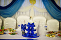 Wedding cake with blue ribbons and figurine of newlyweds on tabl