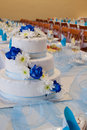 Wedding cake with blue roses on a table Royalty Free Stock Image