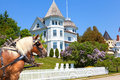 Wedding cake cottage on west bluff road mackinac island a team of horses pulling a carriage pose in front of a victorian home high Royalty Free Stock Photo