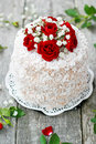 Wedding cake decorated with red roses homemade and white flowers on plate Royalty Free Stock Photos