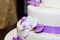 Wedding cake tall with purple ribbon and flower decorations Stock Photography