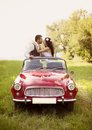 Wedding car with bride and groom gorgeous having fun red retro in nature Stock Photos