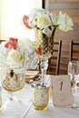 Wedding centerpieces varying sizes and shapes of gold and silver decorative votives holding fresh white and coral roses Royalty Free Stock Photo