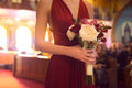 Wedding ceremony day. bridesmaid girl wearing elegant red dress holding flowers bouquet at Wedding ceremony in catholic church. Royalty Free Stock Photo