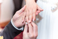 Wedding ceremony groom putting ring on bride s finger Stock Photo
