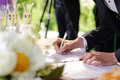 Wedding ceremony groom signing certificate in park Stock Photography