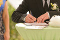 Wedding ceremony groom signing certificate in park Stock Photo
